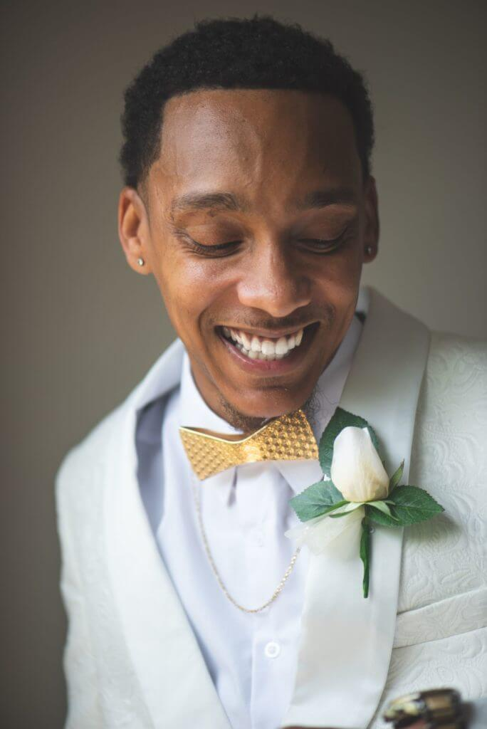 Groom in white suit with yellow bowtie
