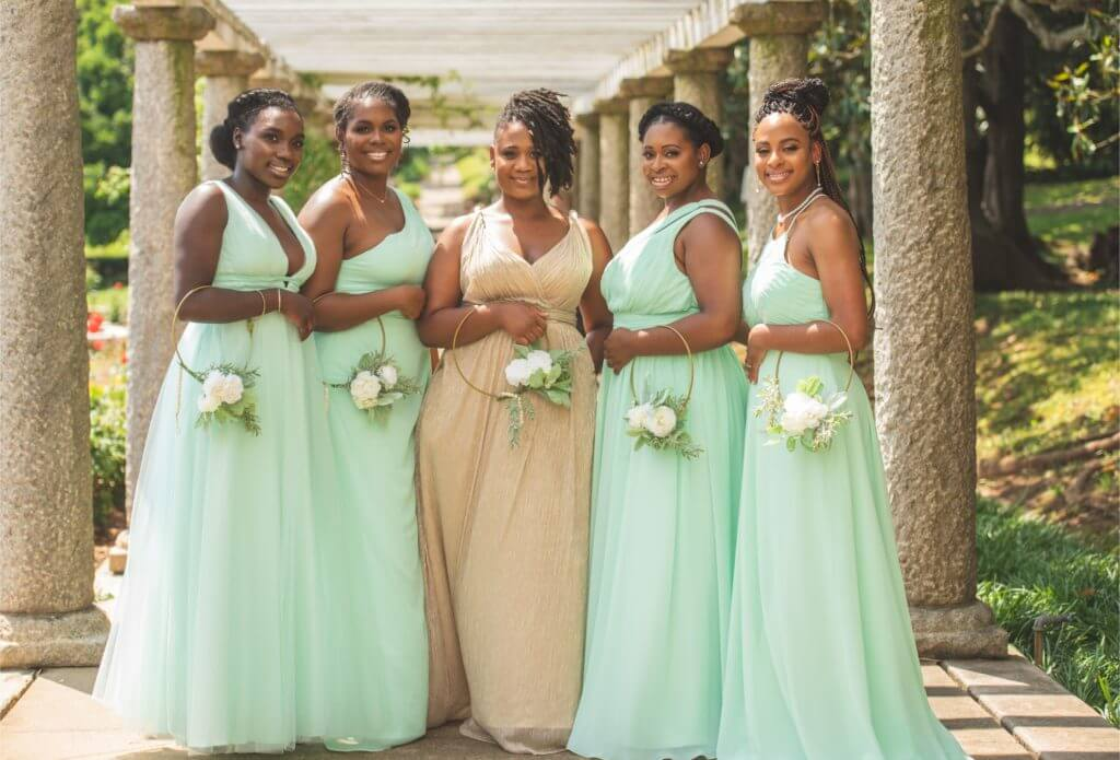 Bridesmaids in tan and mint green dresses against garden background