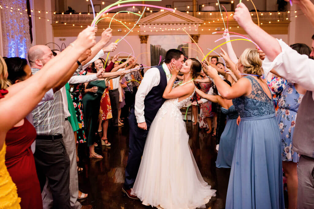 Bride and groom exchange a kiss as wedding guests cheer and wave glow sticks around them
