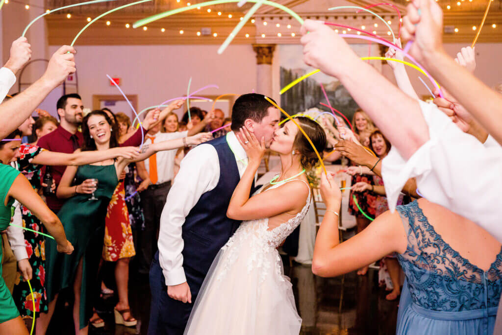 Bride and groom kiss as wedding guests cheer and wave glow sticks around them