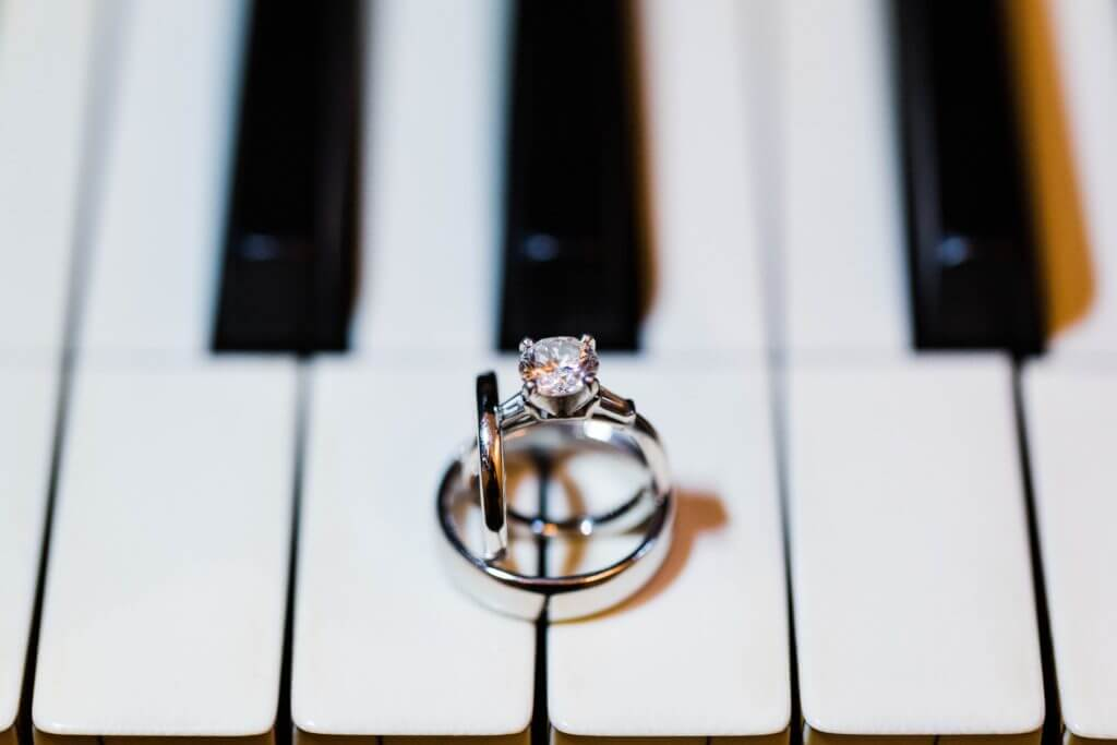 Bride and groom's wedding rings sit on keys of a piano.