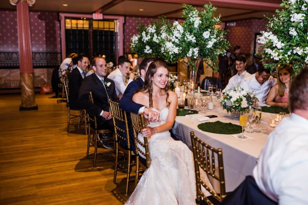 Bride and groom sit at their dinner table at their wedding.