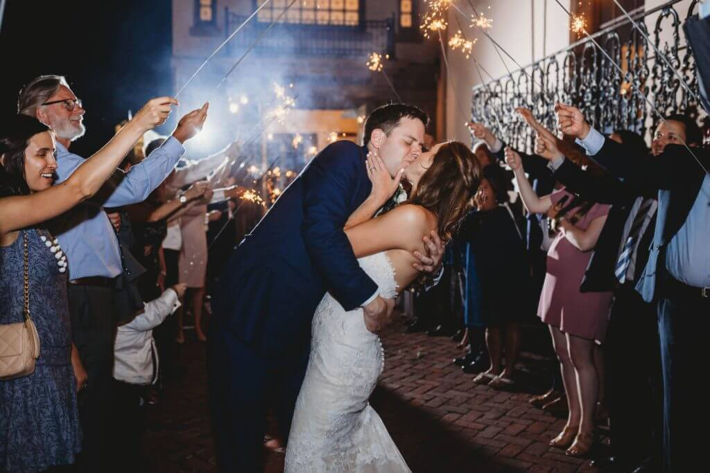 Bride and groom kiss under sparklers held by their wedding guests.