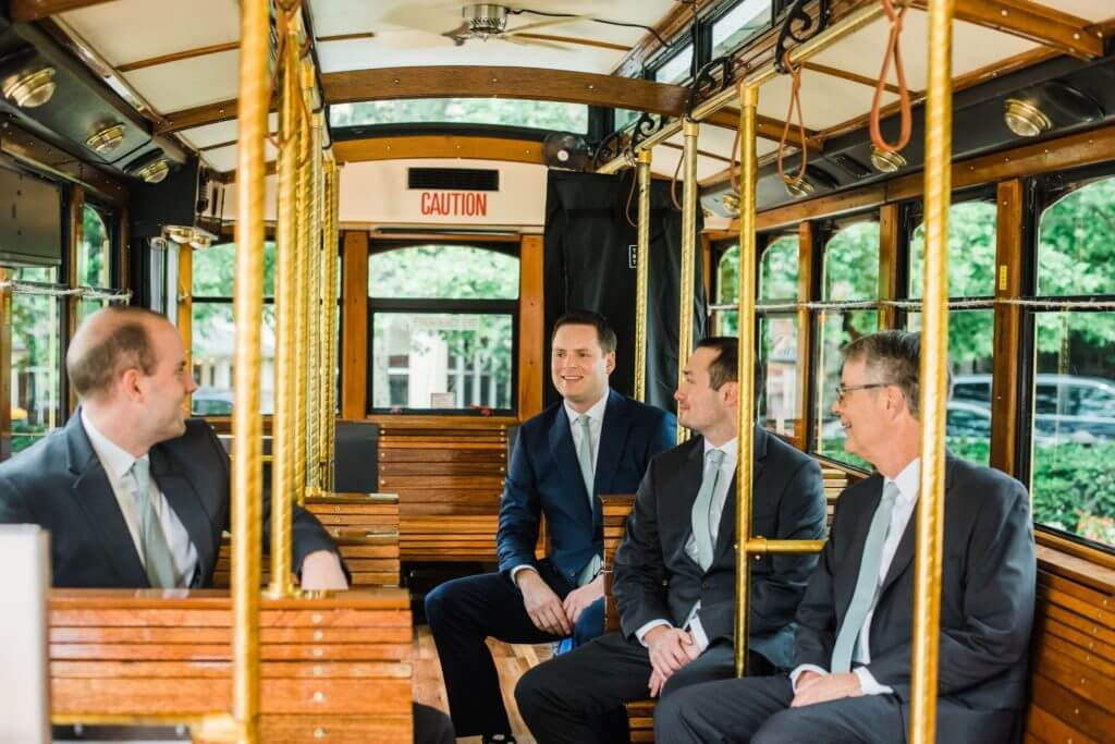 Wedding party of the groom sits in a Richmond Trolley in their suits.