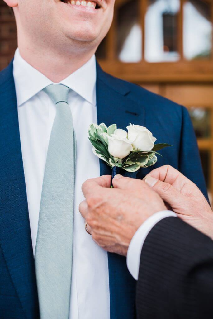 Father of the groom adorns a corsage to the groom's suit jacket.