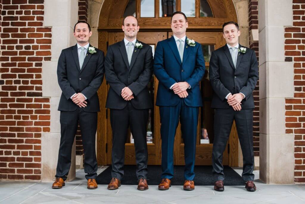 Groom, Will, stands in front of wedding church with groomsmen.