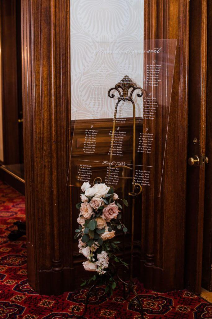 Clear etched acrylic seating chart with flowers at the entrance of dining room at Bolling Haxall House.