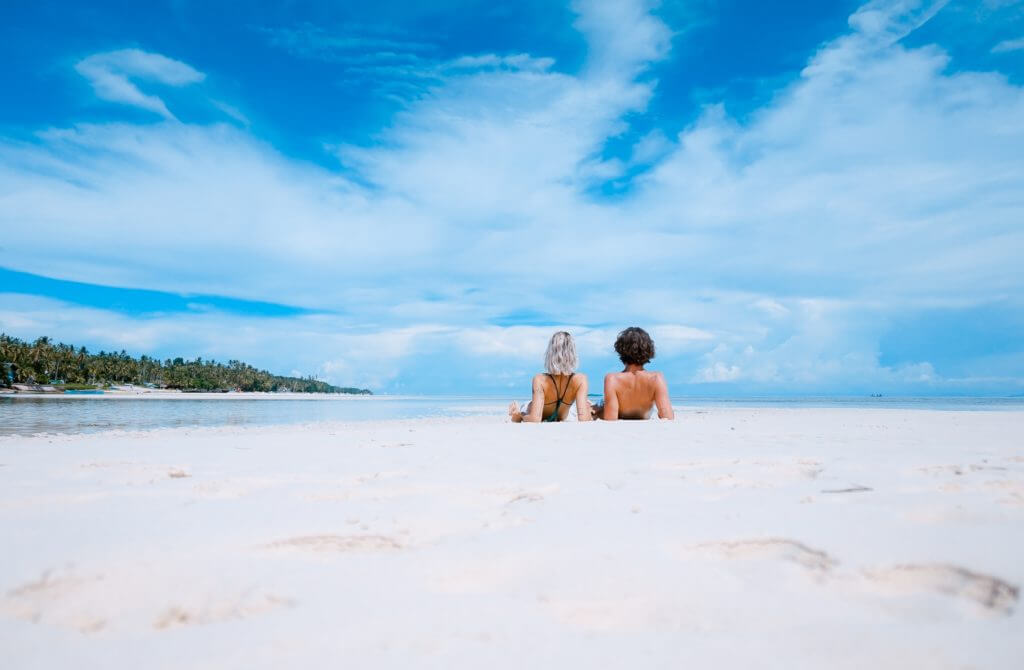 Couple lays back on sand on a beach as they gaze at the water