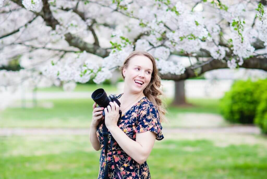 Photographer Emmi Claire holds camera smiling with blossoming tree in the background.