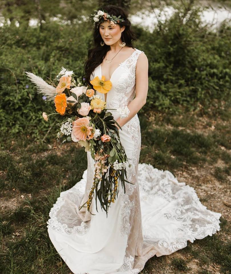 bride stands with multicolored flowers against greenery background