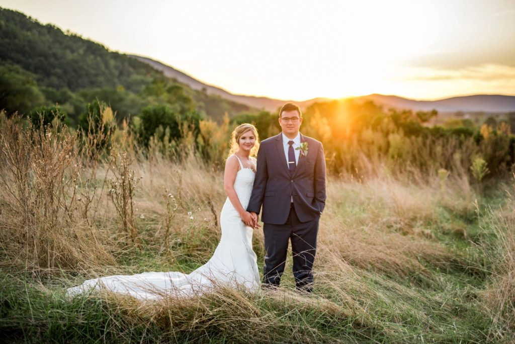 Newlyweds stand in open field with sunset and mountains behind