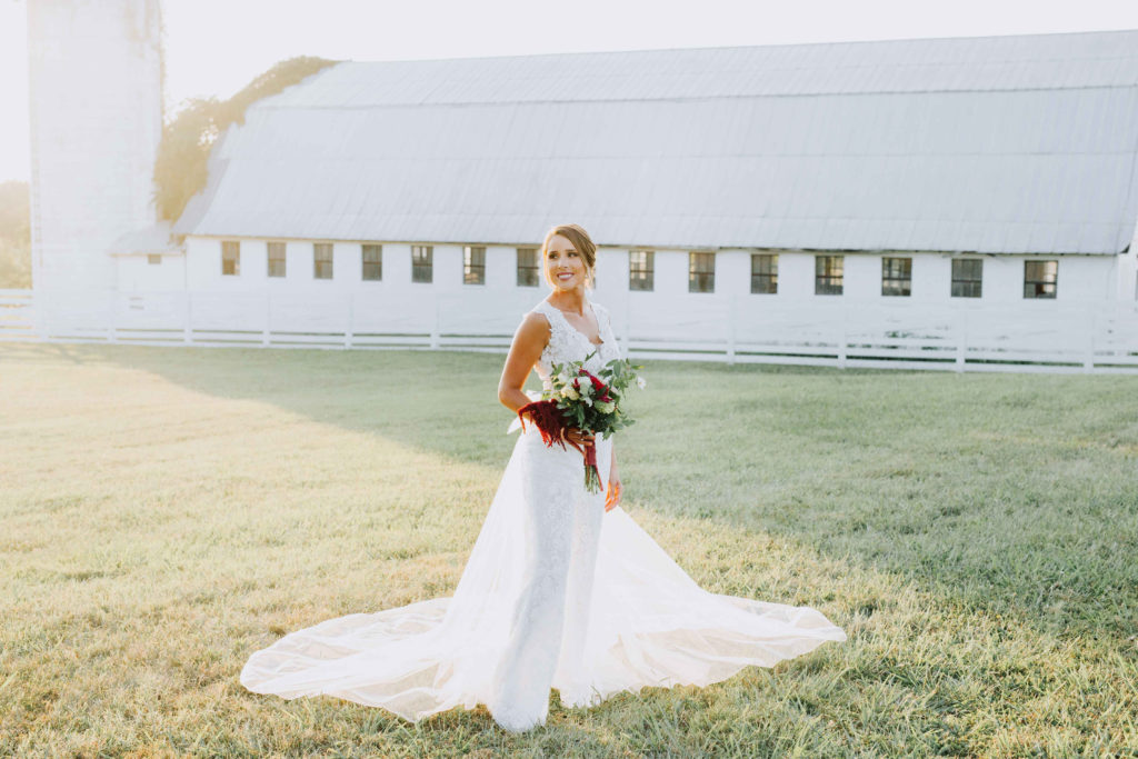 bride stands with red flowers in open field